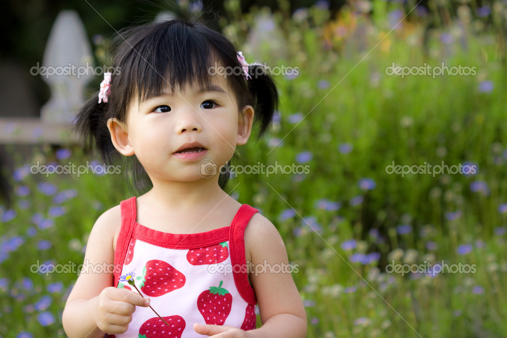 Little Asian chilld hold a flower in her hand — Stock Photo #1378275