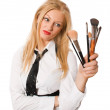 Isolated blonde female looking at makeup brushes — Stock Photo