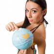Stock Photo: Nude young female pointing at globe isolated