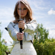 Stock Photo: Young female with samurai sword outdoor