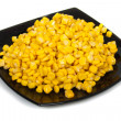 Black plate with corn seeds isolated — Stock Photo