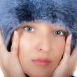 Seductive mature brunette in fur cap — Stock Photo