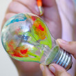 Stock Photo: Multicolor painting light bulb in hand
