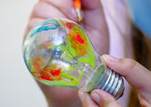 Multicolor painting light bulb in hand — Stock Photo