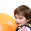 Little girl playing with big orange ball — Stock Photo #1776166