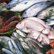 Fresh raw fish presented for sale - Stock Photo