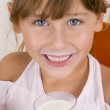 Smiling girl holding glass of milk — Stock Photo #1330214
