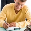 Man smiling while writing — Stock Photo #1347314