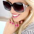 Smiling blonde female wearing sunglasses — Stock Photo