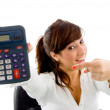 Smiling woman pointing at calculator — Stock Photo
