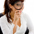 Female looking through lens and smiling — Stock Photo