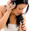 Stock Photo: Young female holding headphone and mic