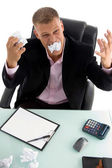 Young angry businessman eating paper — Stock Photo