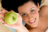 Smiling young woman offering an apple — Stock Photo