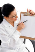 Female doctor indicating writing pad — Stock Photo