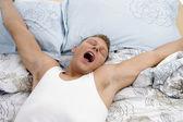 Yawning man stretching his arms — Stock Photo