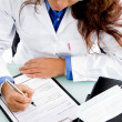Young doctor writing prescription - Stock Photo