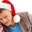 Man with christmas hat talking on mobile - Stock Photo