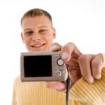 Handsome man showing digital camera — Stock Photo