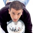 Young guy resting on shiny disco ball - Stock Photo