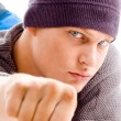 Cool man with winter cap showing fist — Stock Photo