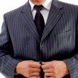 Businessman tucking his coat button — Stock Photo