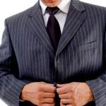 Businessman tucking his coat button — Stock Photo
