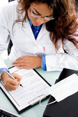 Young doctor writing prescription — Stock Photo