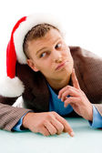 Thinking young man with christmas hat — Stock Photo