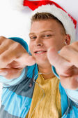 Pointing smiling male with christmas hat — Stock Photo