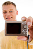 Handsome man showing digital camera — Stock Photo