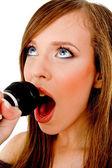 Woman singing into karaoke — Stock Photo