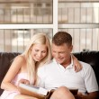 Stock Photo: Couple viewing album and smiling