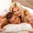 Portrait of young couple in bed — Stock Photo