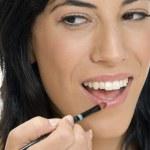 Smiling lady putting lipstick — Stock Photo