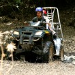 Stock Photo: Couple riding ATV off road