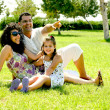Family resting on lush green ground — Stock Photo