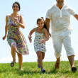 Family running towards the camera — Stock Photo