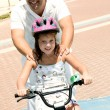Foto Stock: Father supporting daughter while bicycle