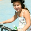 Girl riding bicycle with safety helmet - Stock Photo