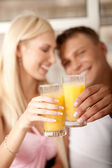 Couple holding juice glass — Stockfoto