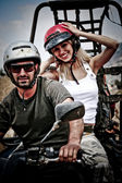 Happy young couple on ATV — Stock Photo