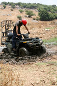 Young man badly stuck in mud with his quad bike — Stock Photo