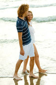 Affectionate couple walking by the sea — Stock Photo