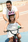 Father supporting daughter while bicycle — Stok fotoğraf