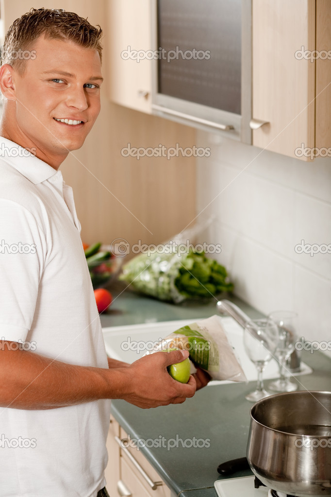 Young guy cooking dinner and facing camera — Stock Photo #1365923