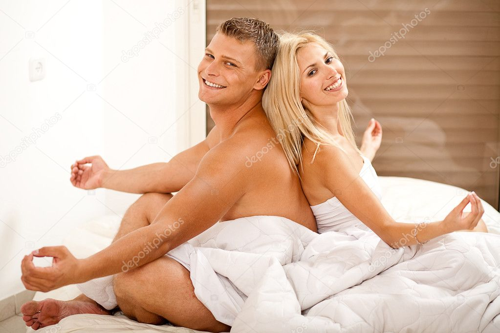 Couple meditating in bed and smiling — Stock Photo #1366147