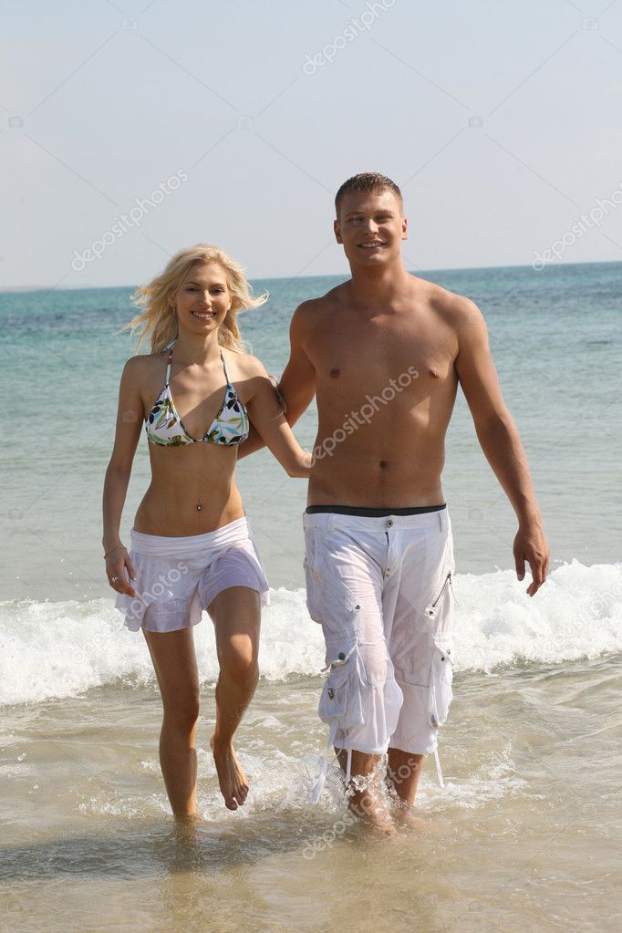 Romantic couple walking down on the beach  Stock Photo #1368247
