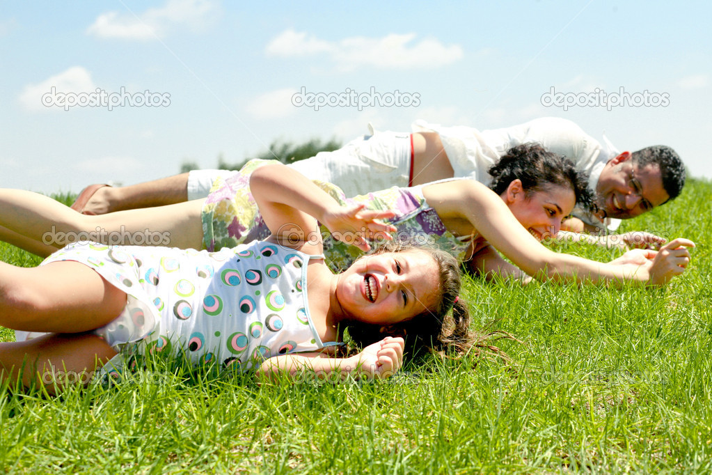 Family lying on lush green ground on sunny day and having fun  Stock Photo #1369522