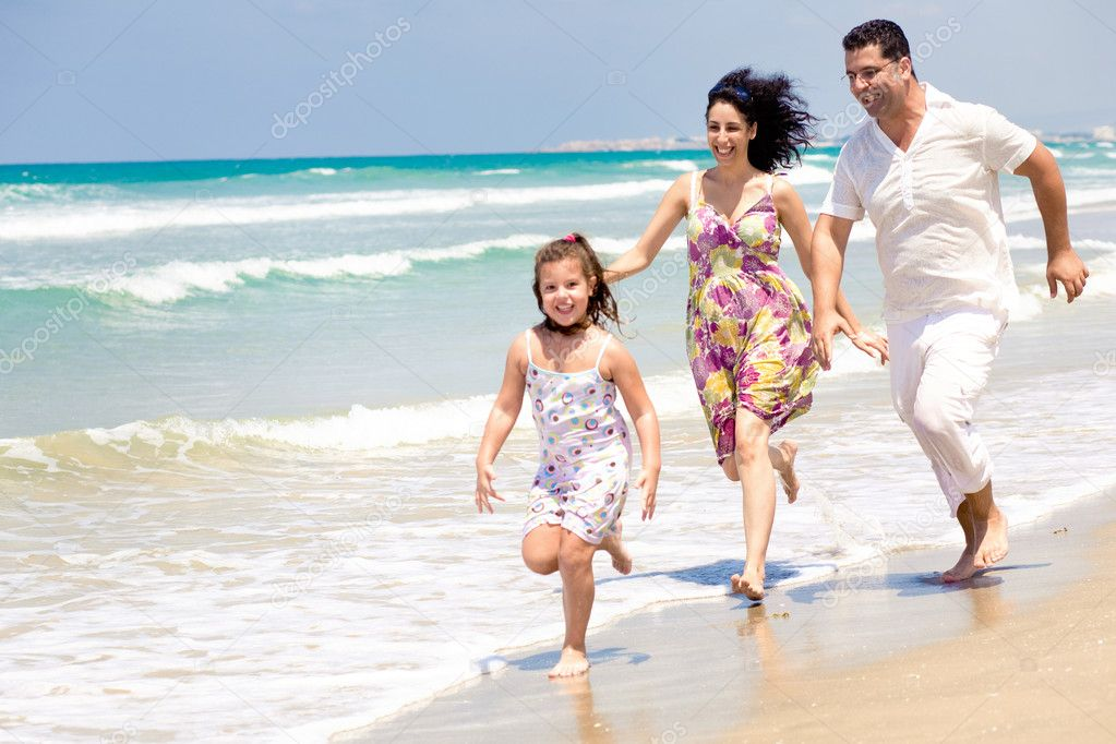 Parents chasing daughter on the beach — Stock Photo #1369607